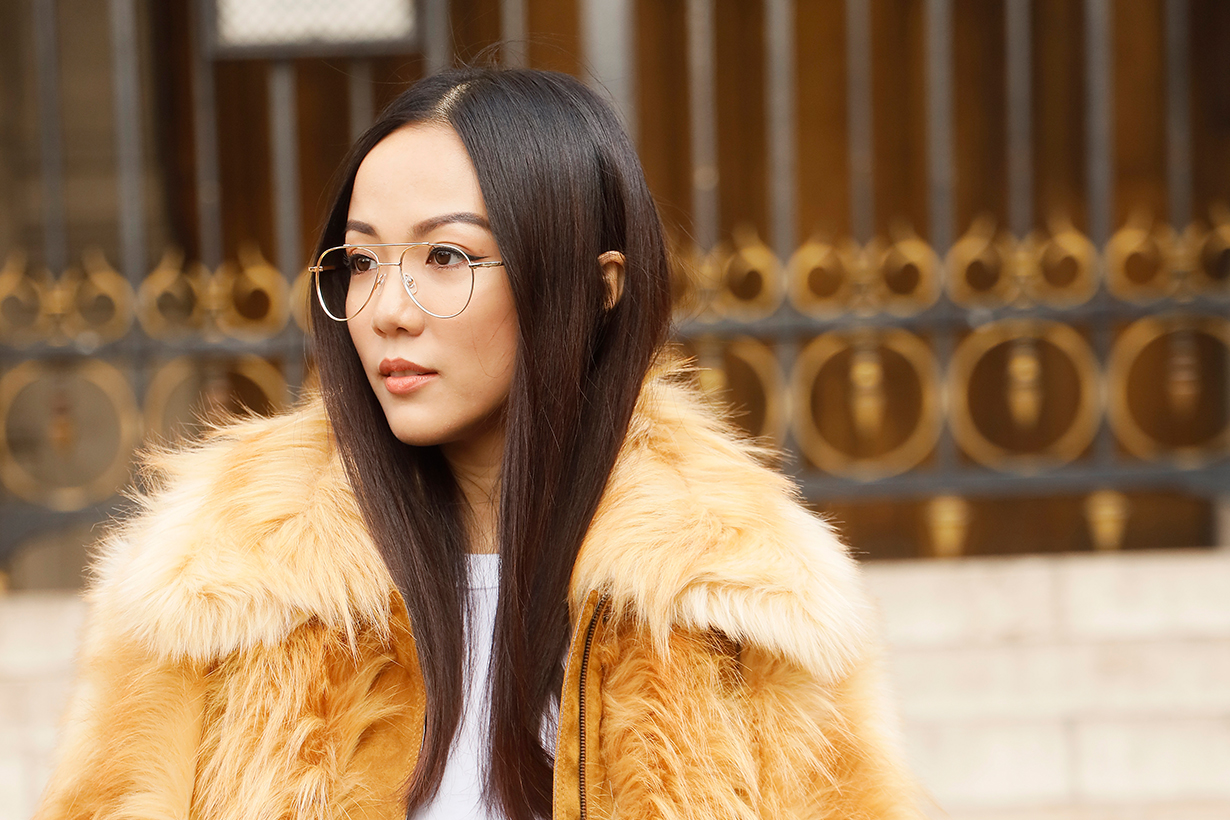 Yoyo Cao wearing a brown fur coat and whit edenim outside Stella McCartney during Paris Fashion Week Womenswear Spring Summer 2020 on September 30, 2019 in Paris, France.