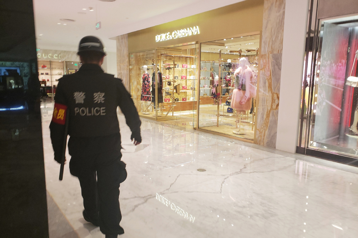 police officer stands guard outside the Dolce & Gabbana store