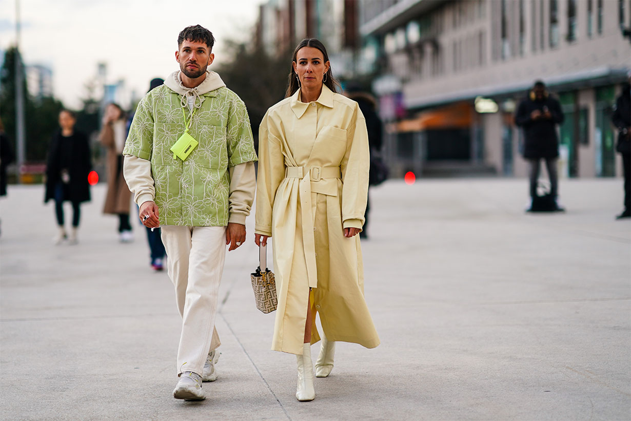 Jean-Sebastien Rocques (L) wears a beige hooded sweatshirt, rings, a pistachio-green short sleeves shirt with white floral embroideries, a neon-green Jacquemus bag, beige jeans, light grey and white sneakers ; Alice Barbier (R) wears earrings, a pale yellow trench coat, a Fendi bucket bag, shiny white square toe booties, outside Jacquemus, during Paris Fashion Week - Menswear F/W Fall/Winter 2020-2021 on January 18, 2020 in Paris, France.