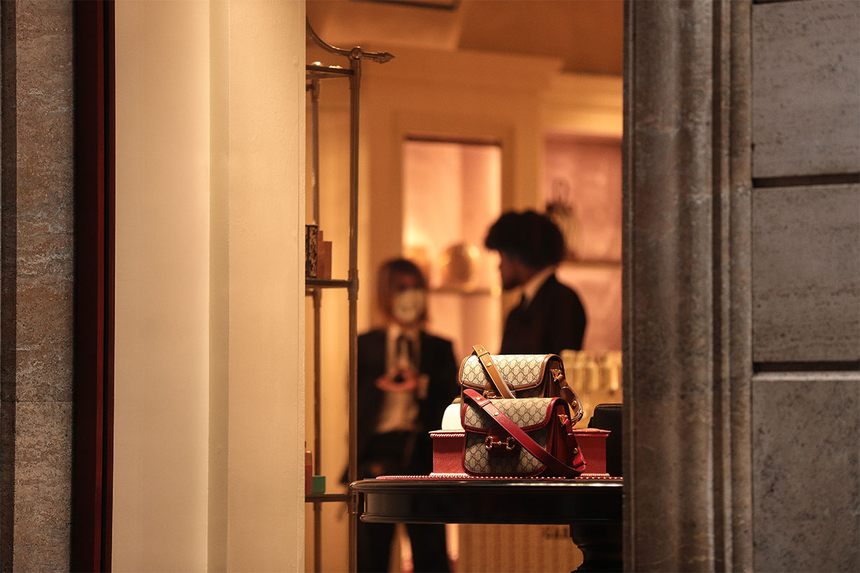 A shop assistant wearing a protective respiratory mask inside a luxury showroom in downtown Rome