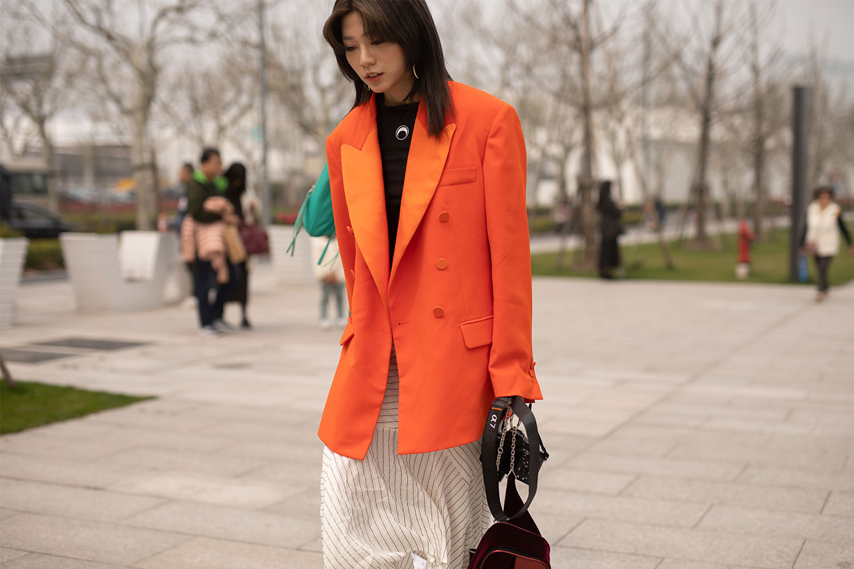 A guest is seen on the street attending Labelhood during Shanghai Fashion Week A/W 2019/2020 wearing orange blazer