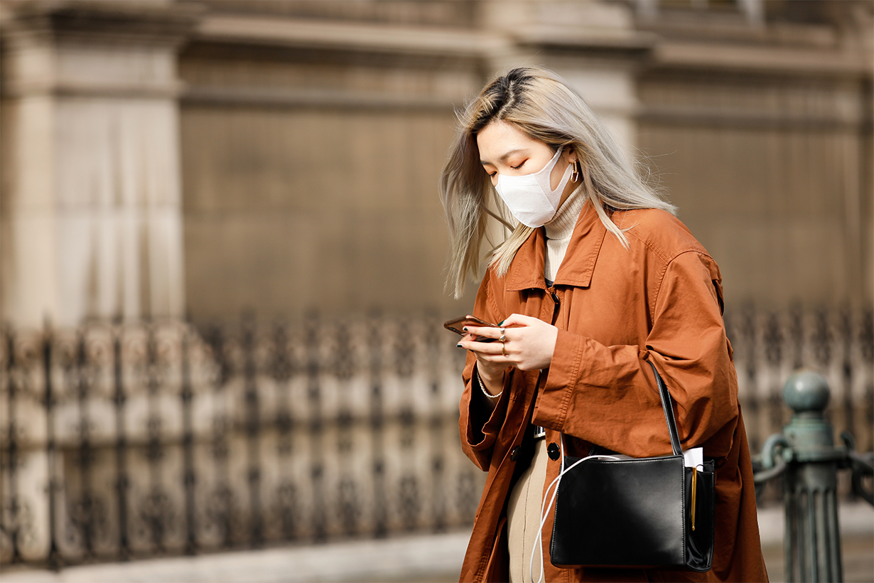 A guest wearing a face mask, tan orange trench outside Vivienne Westwood show during Paris Fashion week Womenswear Fall/Winter 2020/2021 Day Six on February 29, 2020 in Paris, France.