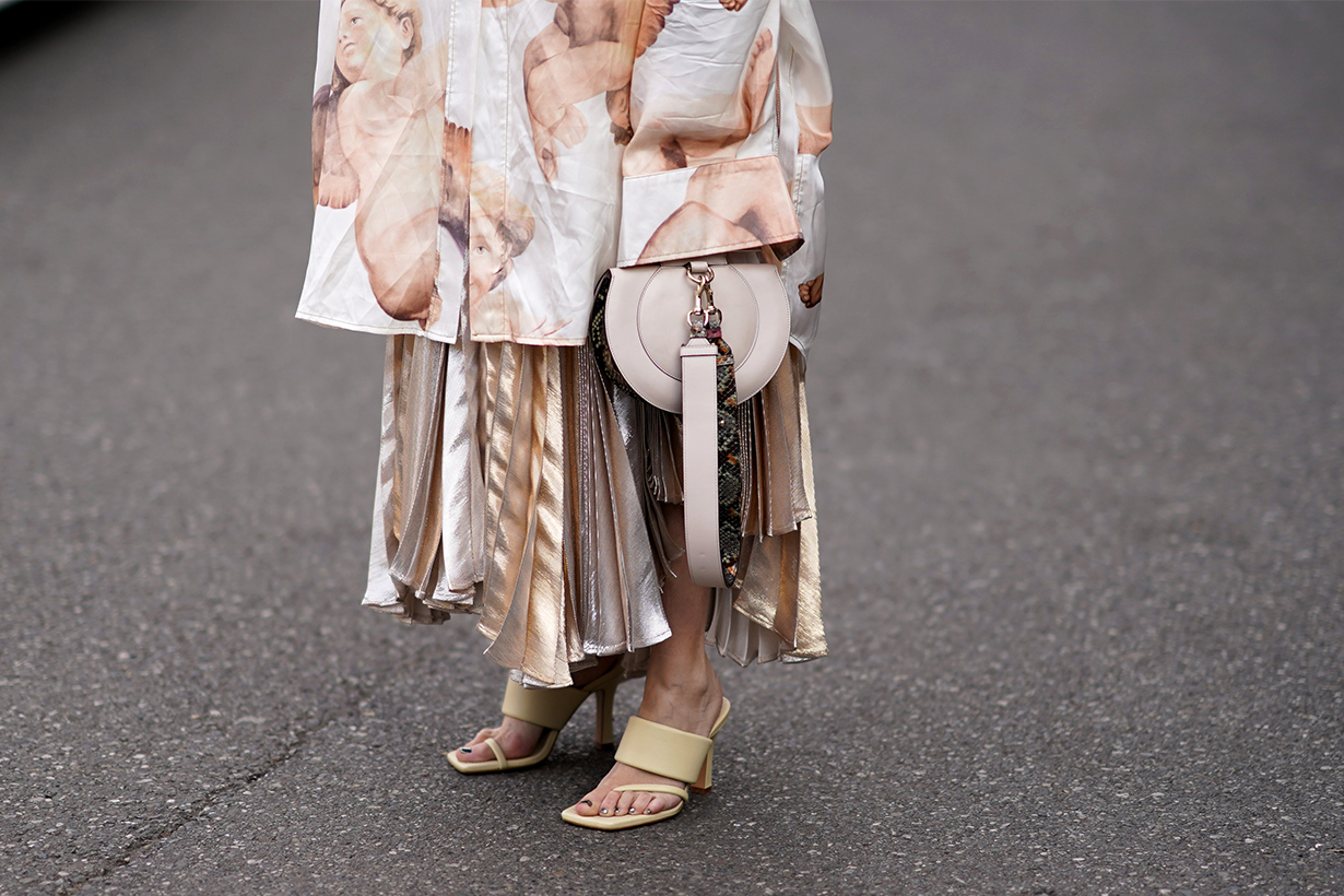 Angela Rozas Saiz wears a large long oversized jacket with long sleeves, a bag with a snake print strap, a pleated dress, cream-color shoes, outside Tod's, during Milan Fashion Week Fall/Winter 2020-2021 on February 21, 2020 in Milan, Italy.