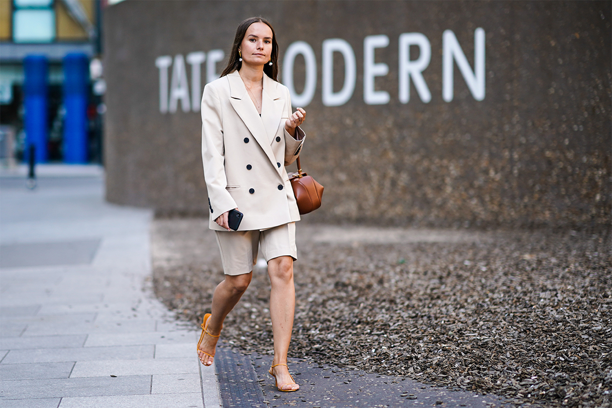 A guest wears earrings, a beige oversized blazer jacket, a brown leather bag, beige shorts, orange shoes, during London Fashion Week September 2019 on September 14, 2019 in London, England.