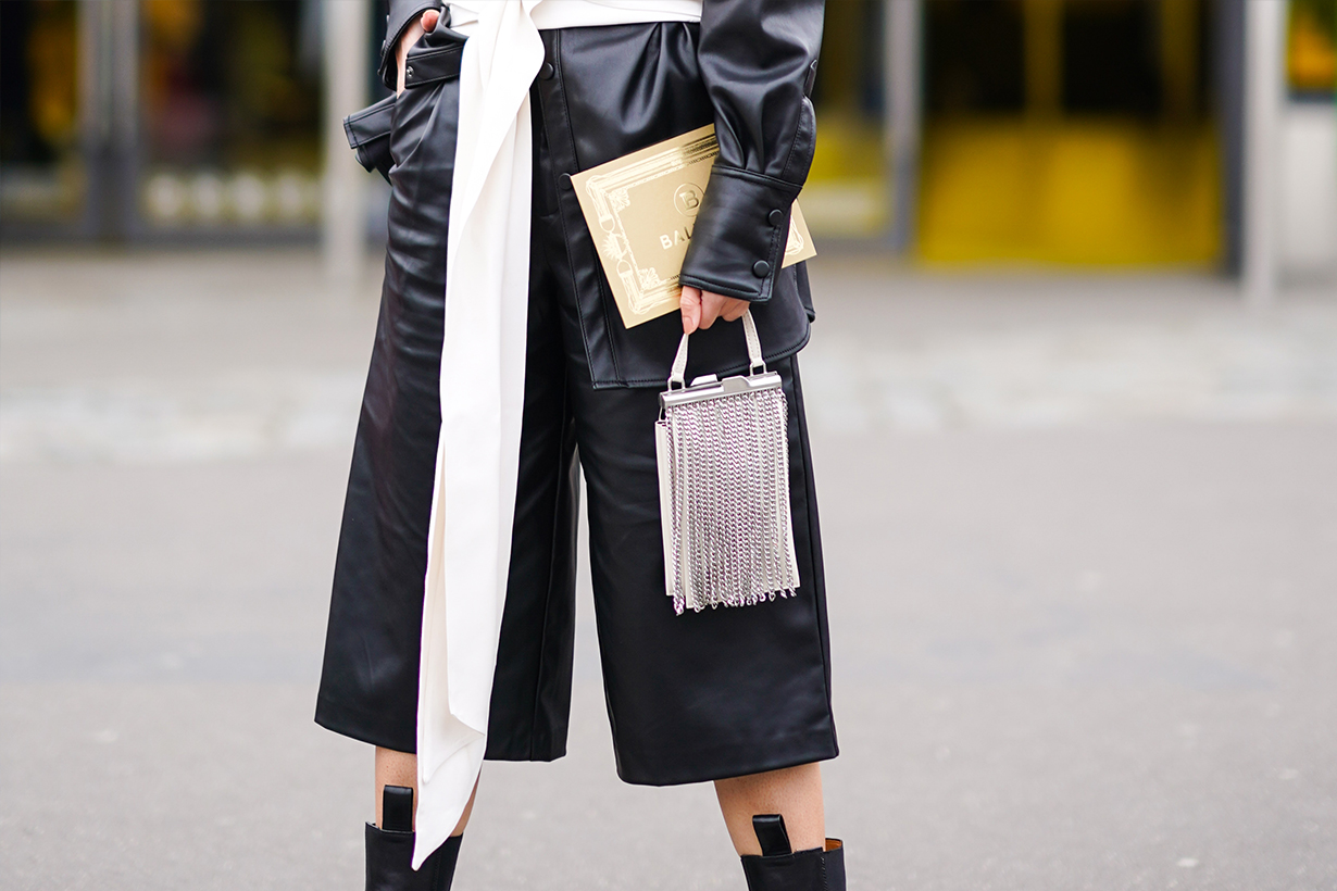A guest a black leather shirt, black leather short pants, a white bag decorated with metallic fringes, outside Balmain, during Paris Fashion Week - Womenswear Fall/Winter 2020/2021, on February 28, 2020 in Paris, France.
