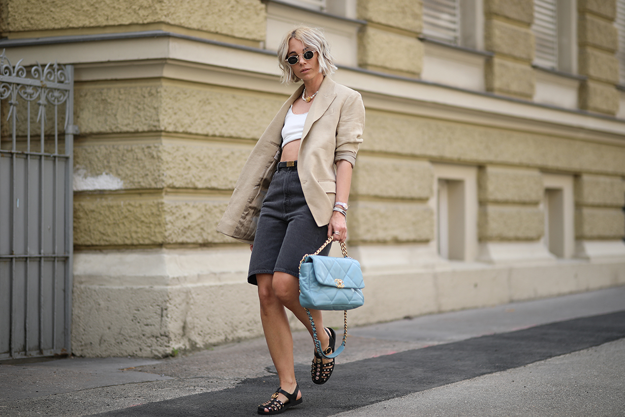 Karin Teigl wearing Gucci sandals, H&M blazer, Chanel bag, Arket jeans short, Skims shirt on May 31, 2020 in Augsburg, Germany.