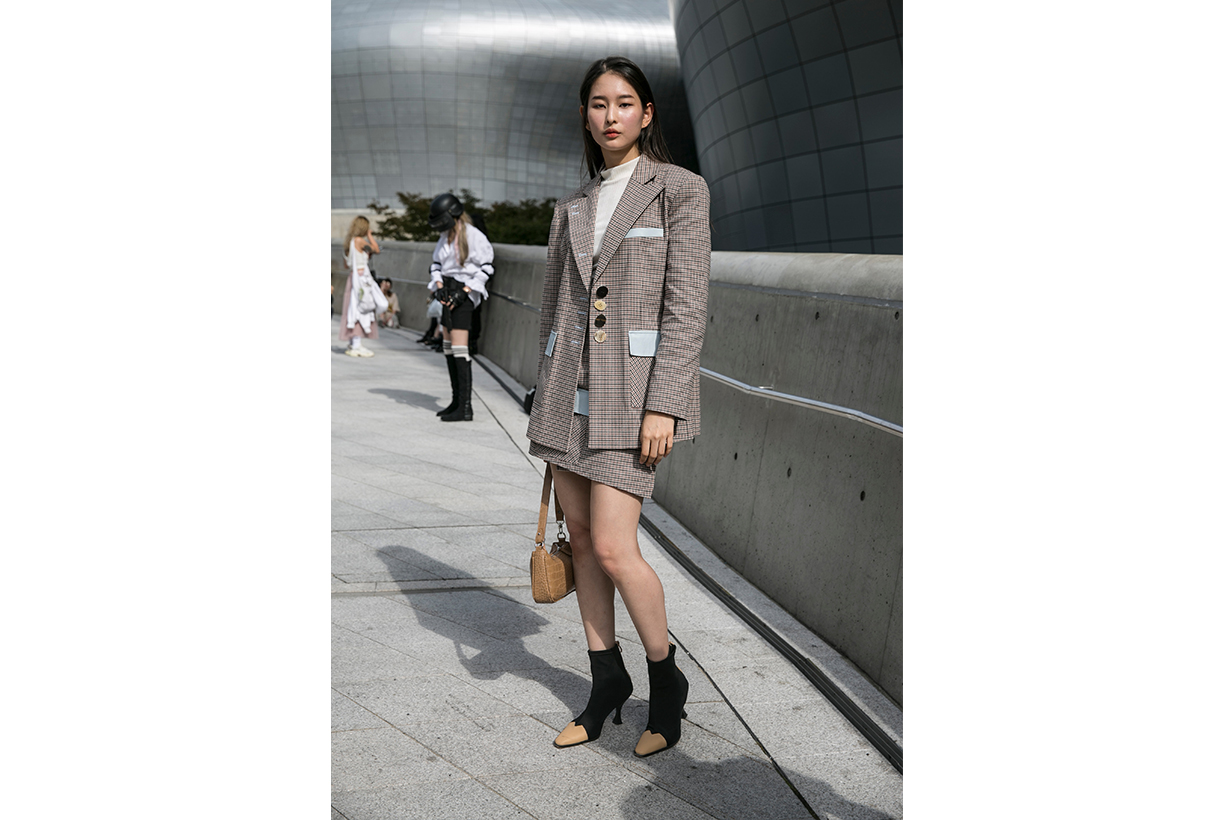 A guest is seen wearing plaid blazer and skirt during the Seoul Fashion Week 2020 S/S at Dongdaemun Design Plaza on October 17, 2019 in Seoul, South Korea.