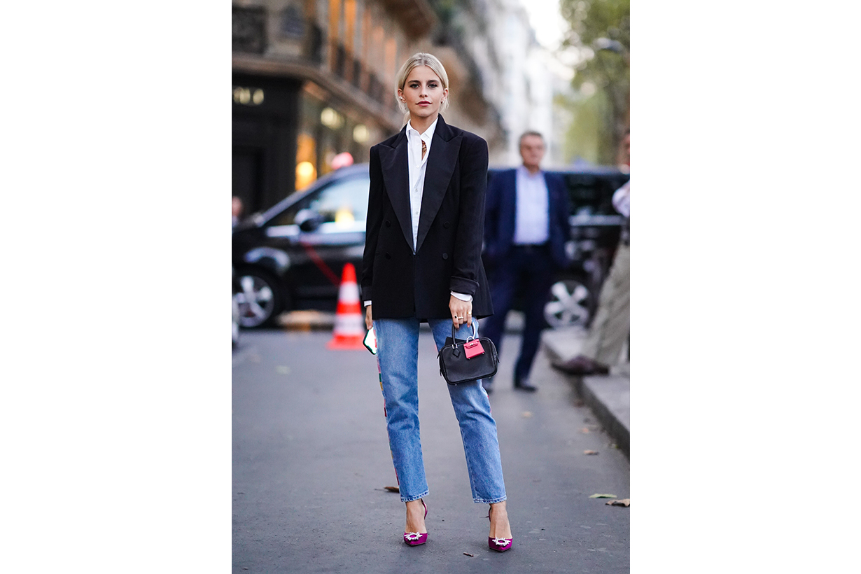Caroline Daur wears a white shirt, a black blazer jacket, a bag with an attached pink mini bag, blue cropped jeans, purple shoes, outside Ralph Lauren, during Paris Fashion Week - Womenswear Spring Summer 2020 on September 28, 2019 in Paris, France.
