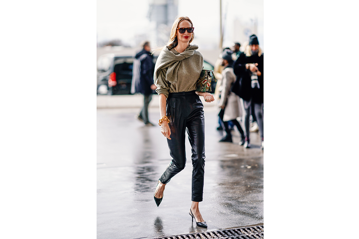 Lauren Santo Domingo wears sunglasses, earrings, a grey sweater, black leather pants, a shiny colorful bag, shiny pumps, outside Giambattista Valli, during Paris Fashion Week Womenswear Fall/Winter 2019/2020, on March 04, 2019 in Paris, France.