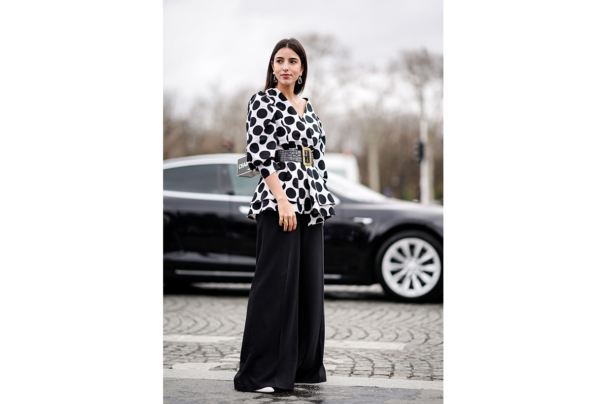 Bettina Looney wears crystal earrings, a white V-neck top with large black dots and ruffled bottom edges, a large black crocodile pattern belt with a brass buckle, black wide-leg pants, a grey metallic color Chanel box bag , outside Chanel, during Paris Fashion Week Womenswear Fall/Winter 2019/2020, on March 05, 2019 in Paris, France.