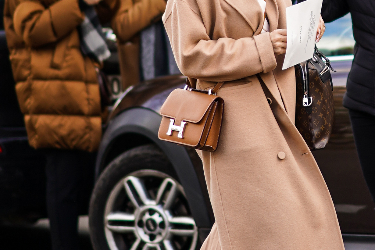 A guest wears a beige coat and a Hermes brown leather bag, outside Elie Saab, during Paris Fashion Week - Womenswear Fall/Winter 2020/2021, on February 29, 2020 in Paris, France.