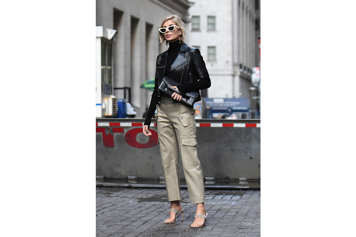 Xenia Adonts is seen wearing a black leather jacket, beige pants, black clutch and white sunglasses outside the Michael Kors show during New York Fashion Week: Fall/Winter 2019 on February 13, 2019 in New York City.