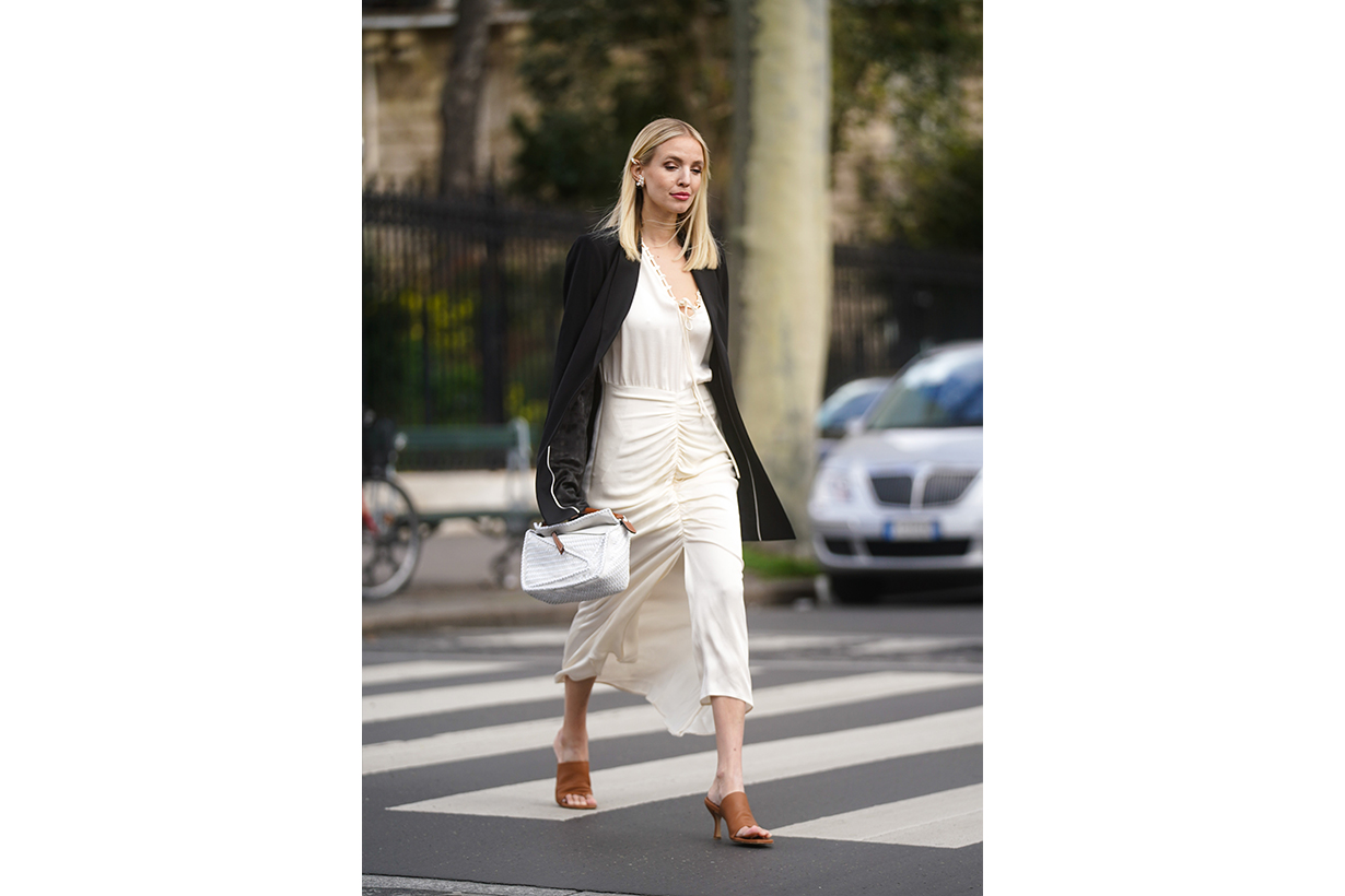 Leonie Hanne wears earrings, a black oversized jacket, a white dress, a white bag, brown pointy shoes, outside Gauchere, during Paris Fashion Week - Womenswear Fall/Winter 2020/2021 on March 03, 2020 in Paris, France.