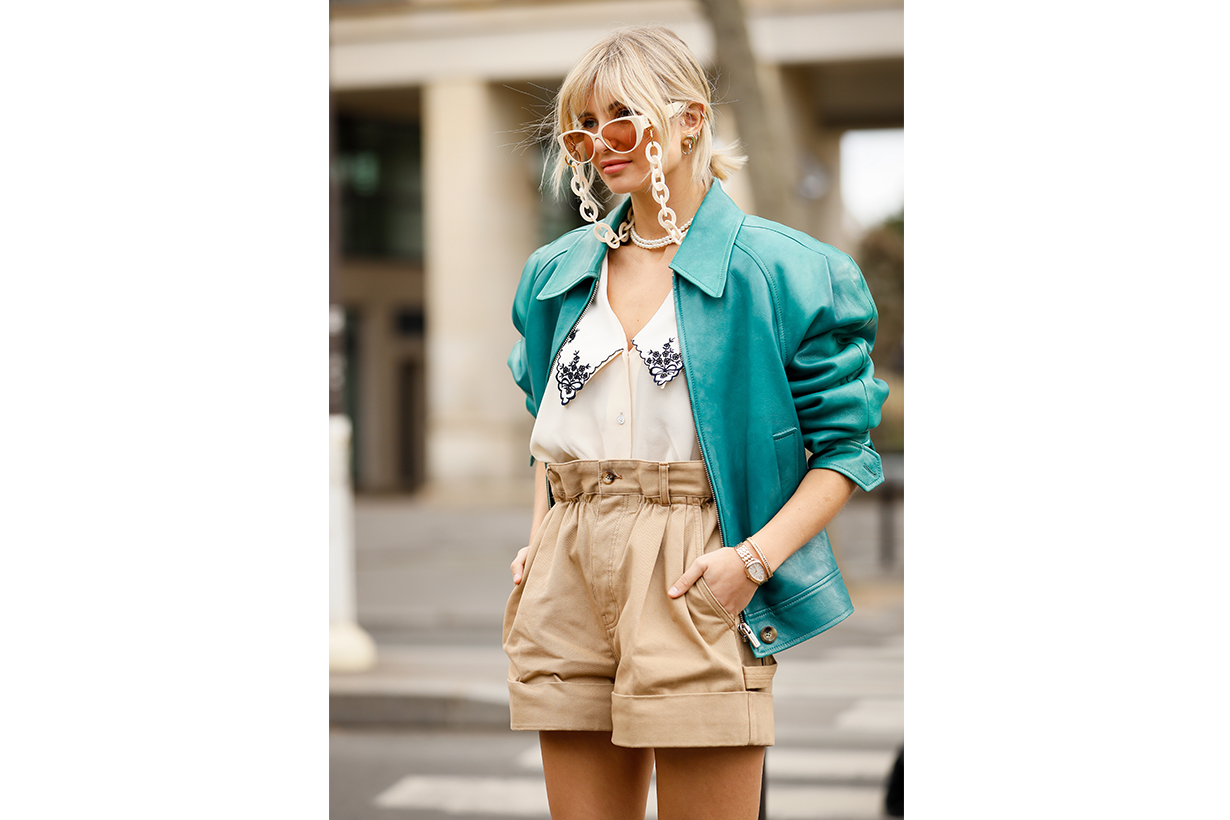 Xenia Adonts wearing Miu Miu embroidery shirt, green leather jacket, beige shorts, black socks beige heels, ivory sunglasses with chain outside the Miu Miu show during Paris Fashion Week Womenswear Fall/Winter 2020/2021 Day Nine on March 03, 2020 in Paris, France.