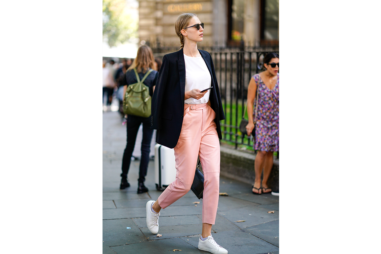 A guest wears a black blazer jacket, pink pants, white sneakers shoes, during London Fashion Week September 2018 on September 17, 2018 in London, England.