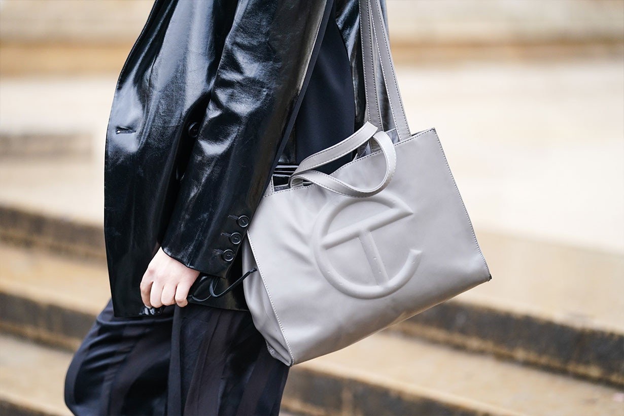 A guest wears a black leather jacket and a gray bag with a T logo, outside Ann Demeulemeester, during Paris Fashion Week - Womenswear Fall/Winter 2020/2021, on February 27, 2020 in Paris, France.