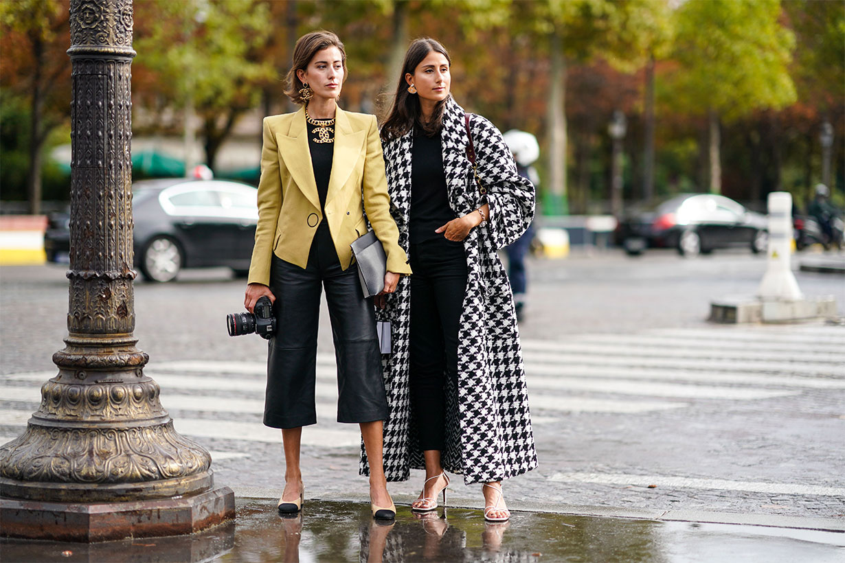 Sylvia Haghjoo (L) wears Chanel earrings, a Chanel necklace, a yellow jacket, a black top, black leather wide-legs crop pants, a grey clutch, Chanel slingback pumps, holds a Canon camera with a 24-70mm zoom lens ; Julia Haghjoo (R) wears Chanel earrings, a bracelet, a black and white houndstooth oversized coat, a black top, black crop pants, white heeled sandals, outside Chanel, during Paris Fashion Week - Womenswear Spring Summer 2020, on October 01, 2019 in Paris, France.