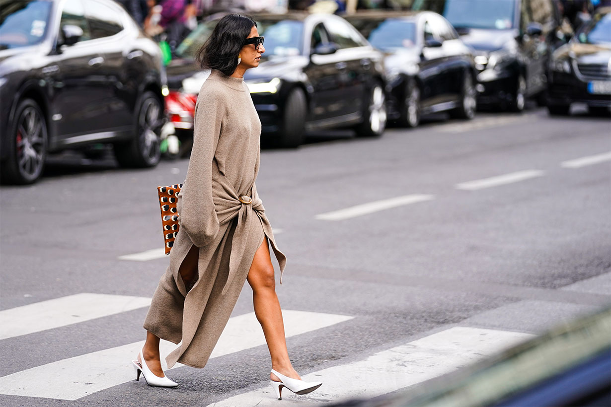 A guest wears sunglasses, earrings, a sand-color long sleeves knit dress slit on the sides, white pointy slingback heels, outside Giambattista Valli, during Paris Fashion Week - Womenswear Spring Summer 2020, on September 30, 2019 in Paris, France.