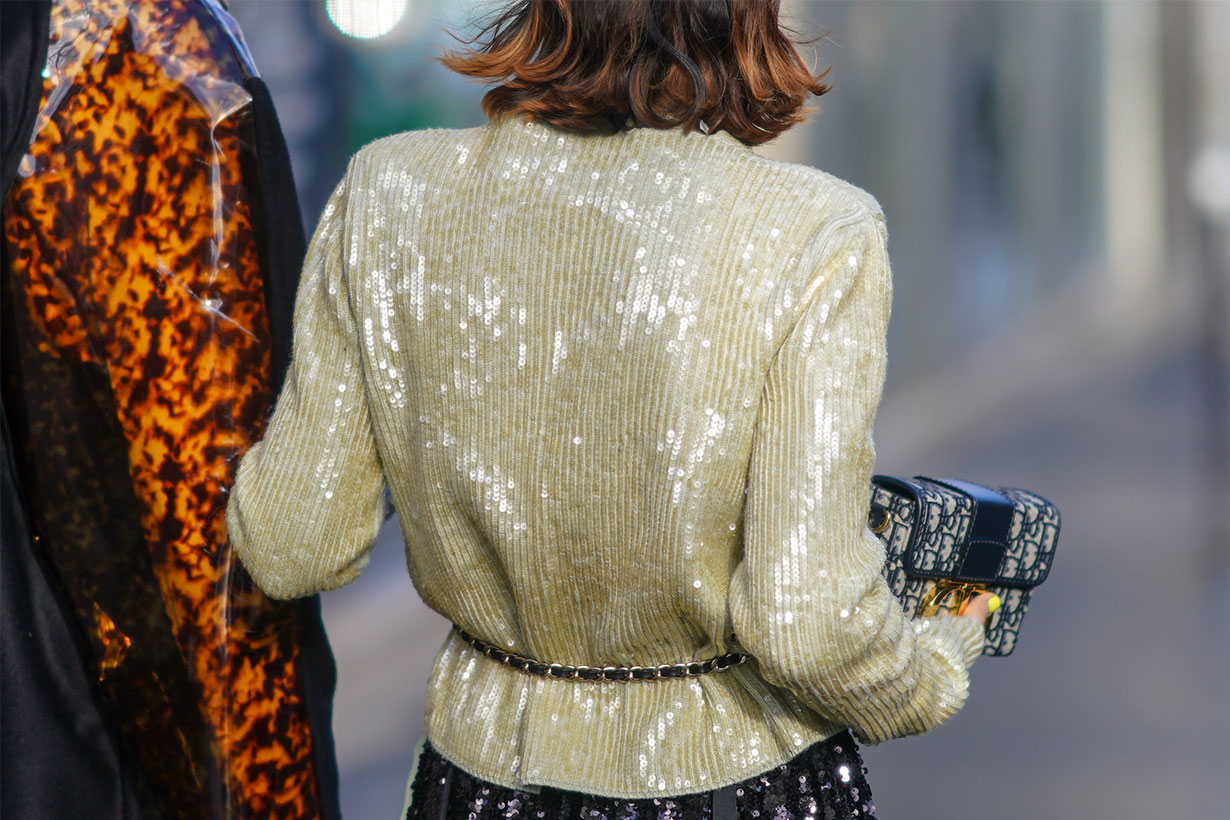 A guest wears a glittering pale yellow sequined jacket, a glittering black sequined skirt, a Christian Dior monogram clutch, outside Lanvin, during Paris Fashion Week - Womenswear Fall/Winter 2020/2021, on February 26, 2020 in Paris, France.