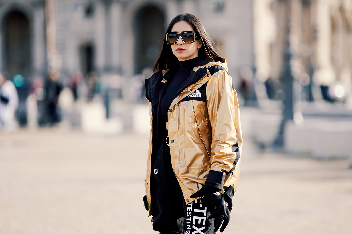 A guest wears a golden shiny bomber winter jacket from The North Face x Supreme, Off-White black pants, a cropped top, outside Off-White, during Paris Fashion Week Menswear F/W 2019-2020, on January 16, 2019 in Paris, France.