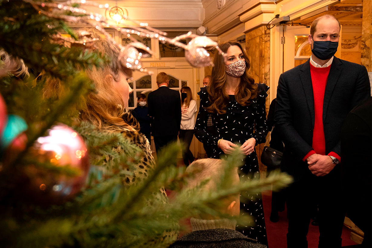 Wearing protective face coverings to combat the spread of the coronavirus, Britain's Prince William, Duke of Cambridge (R) and Britain's Catherine, Duchess of Cambridge (2nd R) speak with guests at a special pantomime performance of The National Lotterys Pantoland at London's Palladium Theatre in London on December 11, 2020, to thank key workers and their families for their efforts throughout the pandemic. (Photo by Aaron Chown / POOL / AFP)